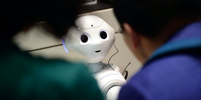 HANOVER, GERMANY - MARCH 20: The robot 'Pepper' speaks with visitors at the IBM stand at the CeBIT 2017 Technology Trade Fair on March 20, 2017 in Hanover, Germany. 'Pepper' has a face detection and is either used to greet Hotel guests during arrival or can be personalized by his owner to help in the household. The 2017 CeBIT will run from March 20-24. (Photo by Alexander Koerner/Getty Images)