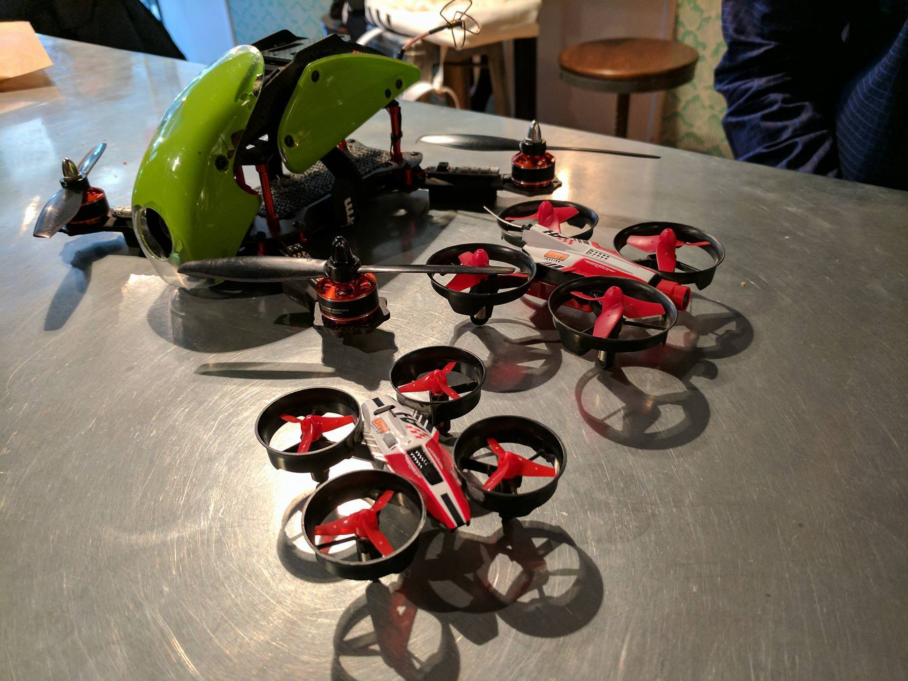 The green drone in the back is a regular racing drone, which can accelerate from 0 to 60 mph.  The red and black drone in the back is a micro drone, also used for racing. The drone in the front is an entry-level drone, which is smaller than the other two drones.  Unlike the other two drones, the entry-level drone does not have a camera and is flown at line-of-sight.