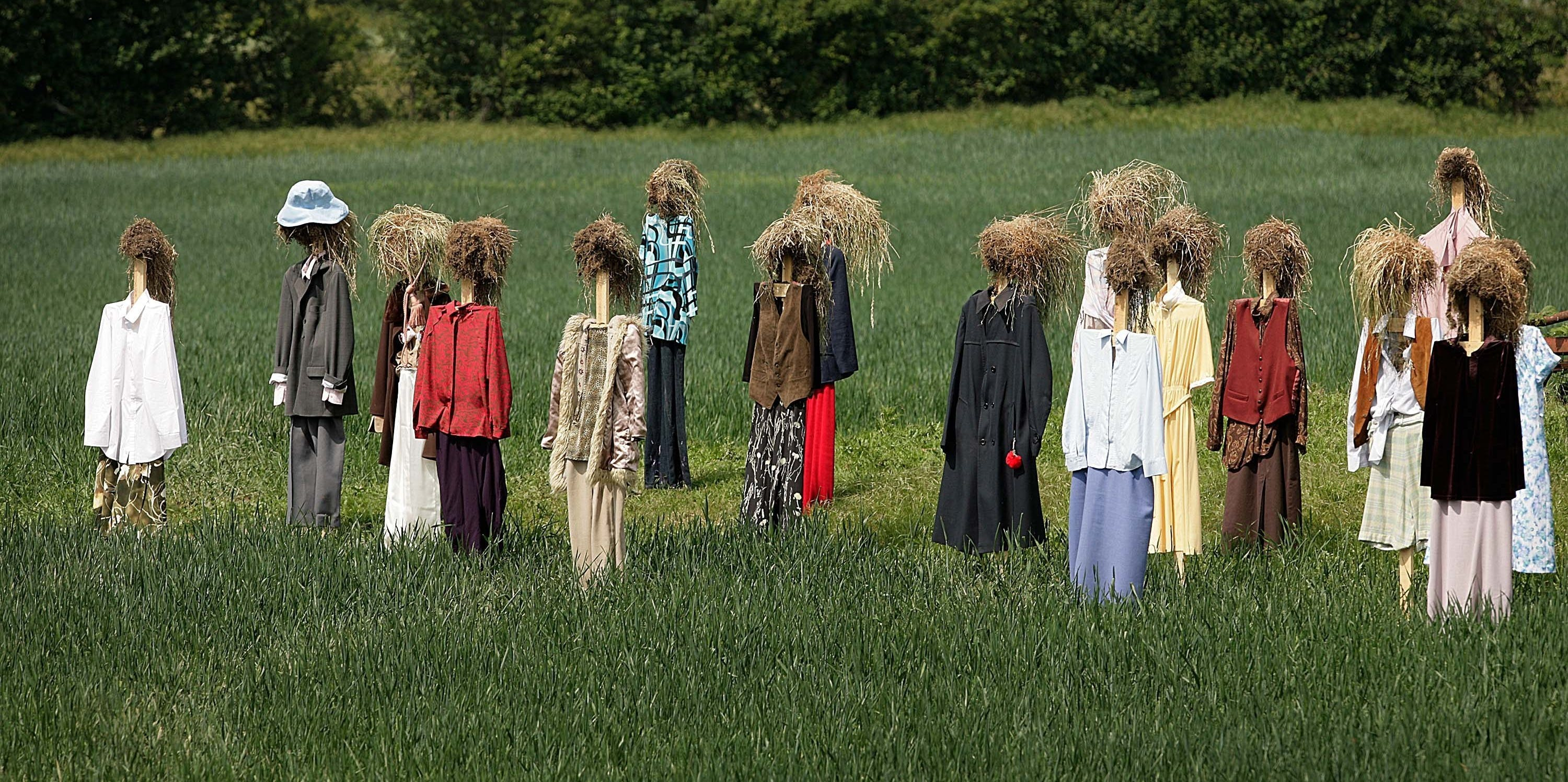 Locals look at Finnish artist Reijo Kela's scarecrow installation 'Hei People'  on May 25, 2007 in Shorne, England. The Finnish word Hei means hello and Kela has installed 130 scarecrows at Amhurst Fort in Chatham and a further 200 in a wheat field near the village of Shorne, Kent. 646 scarecrows will appear in surprise installations all over North Kent in the next few weeks.