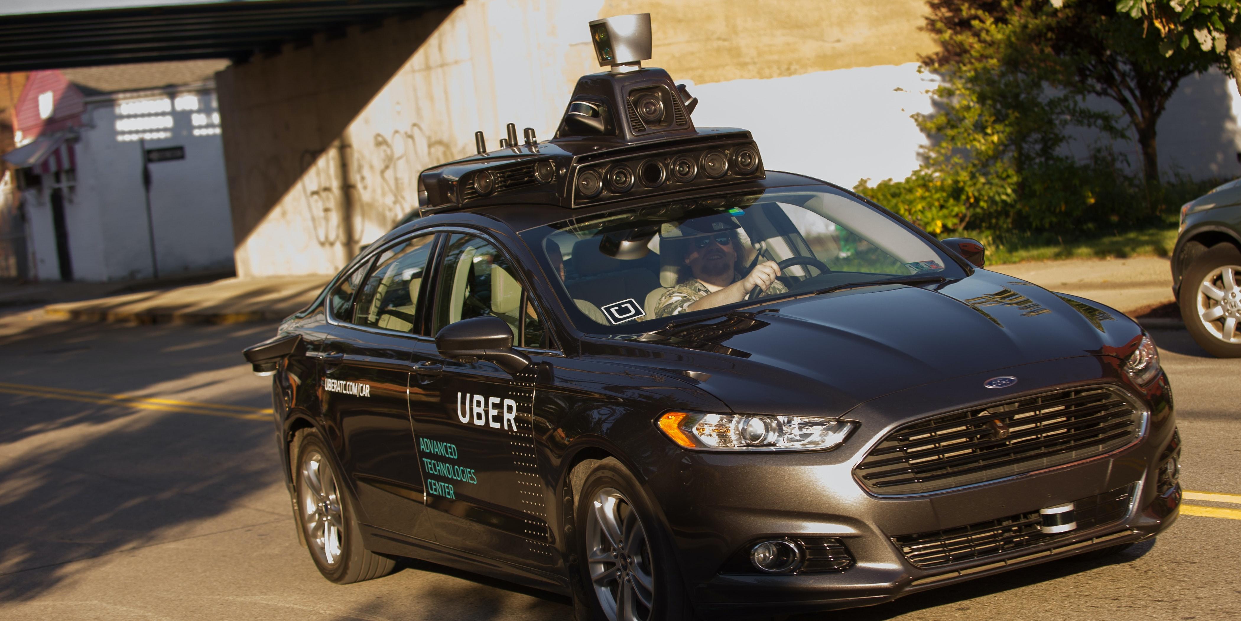 An Uber driverless Ford Fusion drives down Pittsburgh's Smallman Street.