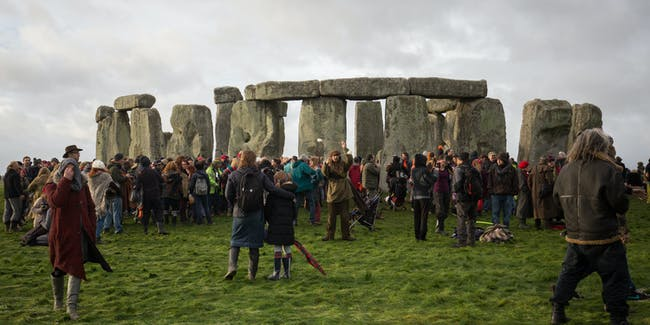AMESBURY, ENGLAND - DECEMBER 22:  People walk around the outside of the stones as druids, pagans and revellers gather in the centre of Stonehenge, hoping to see the sun rise, as they take part in a winter solstice ceremony at the ancient neolithic monument of Stonehenge near Amesbury on December 22, 2015 in Wiltshire, England. Despite a forecast for rain, a large crowd gathered at the famous historic stone circle, a UNESCO listed ancient monument, to celebrate the sunrise closest to the Winter Solstice, the shortest day of the year. The event is claimed to be more important in the pagan calendar than the summer solstice, because it marks the 're-birth' of the Sun for the New Year.  (Photo by Matt Cardy/Getty Images)