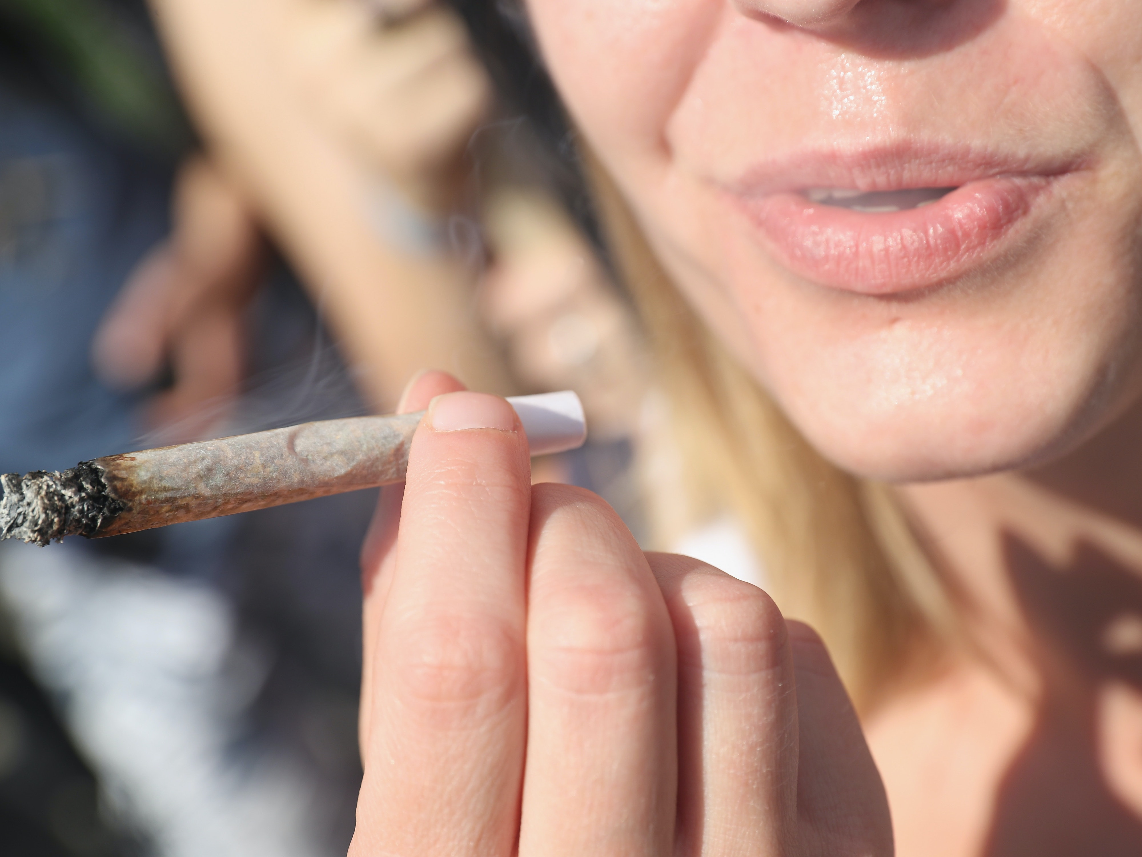 BERLIN, GERMANY - AUGUST 13:  An activists smokes a marijuana joint prior to marching in the annual Hemp Parade (Hanfparade) on August 13, 2016 in Berlin, Germany. German proponents of cannabis legalization are hoping that the legalization in several states in the USA in recent years will increase the likelihood of legalization in Germany.  (Photo by Sean Gallup/Getty Images)