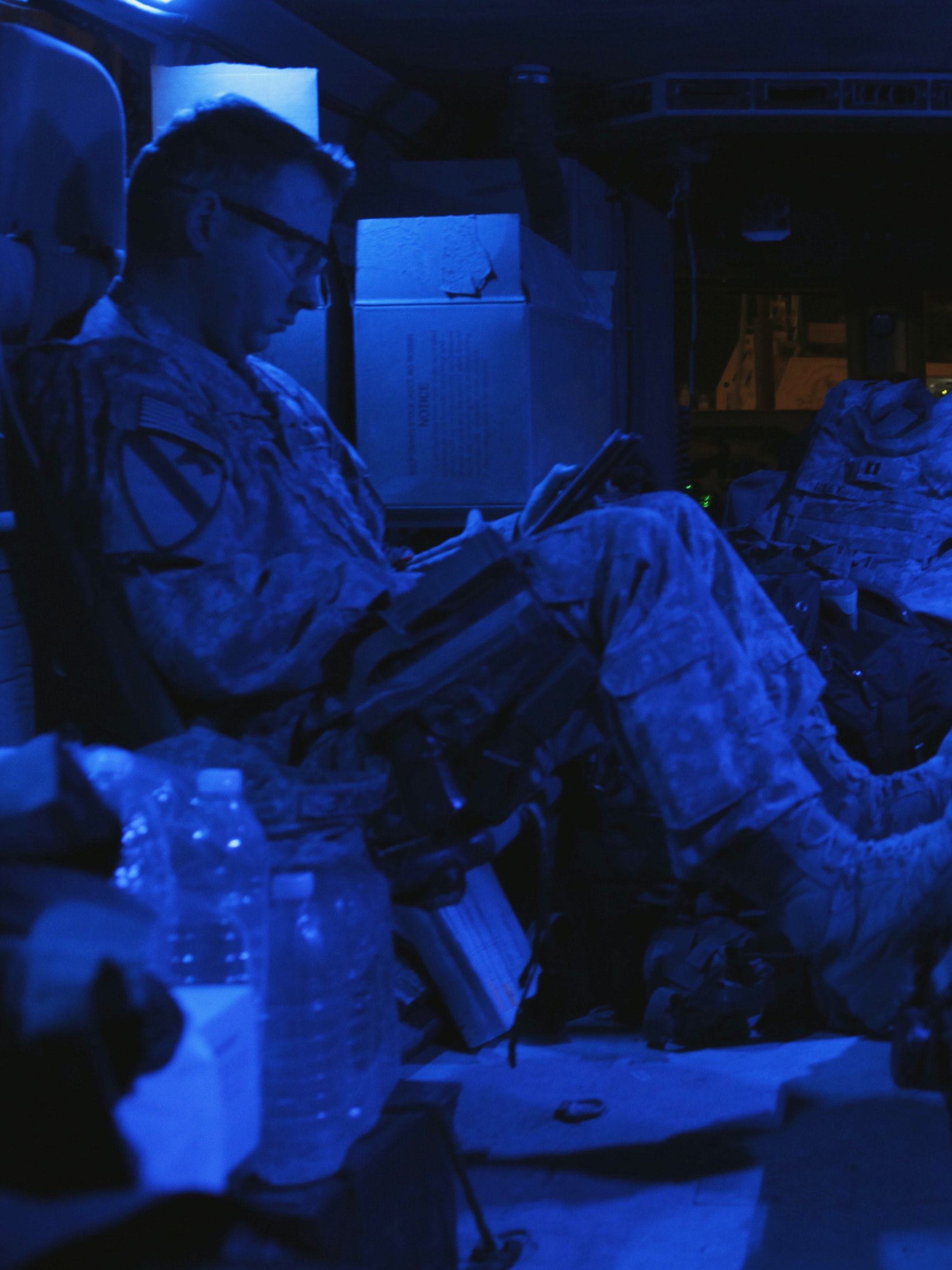 Captain Chris Prange of the 3rd Brigade Combat Team, 1st Cavalry Division reads a book in the back of a Mine Resistant Ambush Protected vehicle.