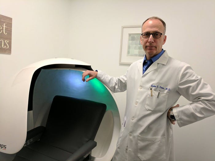 Dr. Jordan Stern, founder and CEO of BlueSleep, stands next to a sleep pod in his office, which has music and light to help users fall asleep or take naps.