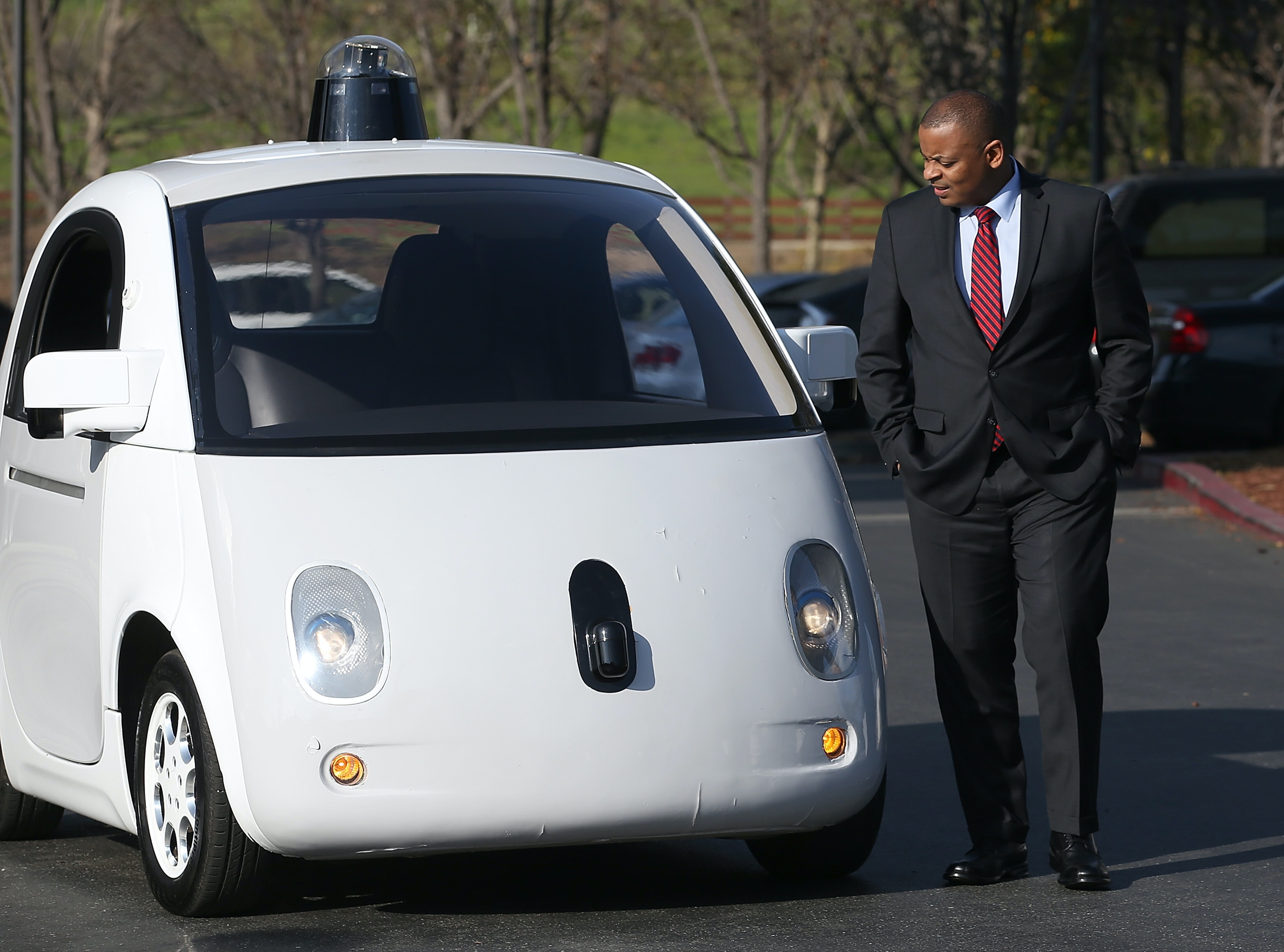 Transportation Secretary Anthony Foxx inspects a Google self-driving car.