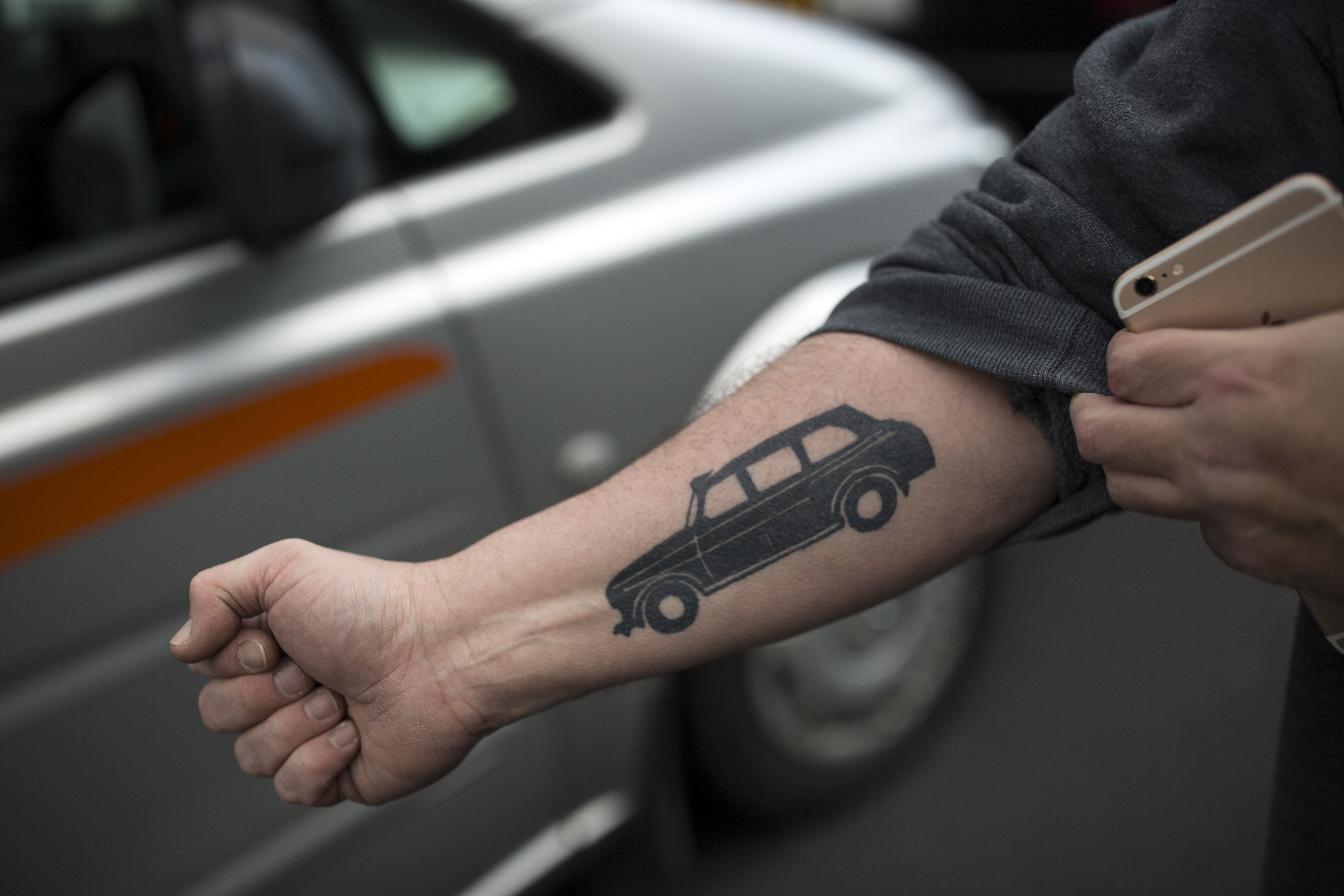 A man shows his tattoo of a London black cab as London taxi drivers stage a protest against Uber's practices on February 10, 2016.