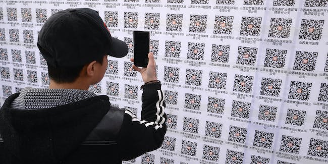 TAIYUAN, CHINA - MARCH 06:  (CHINA OUT) A job seeker scans QR codes during the 2nd Shanxi Exhibition Hall Job Fair on March 6, 2015 in Taiyuan, Shanxi province of China. A new mode of 'Offline 2 Online' recruitment appeared in east China's Shanxi's Taiyuan that businesses launched recruitment information through Wechat QR code and what job seekers should do was to scan the QR codes and posted resumes on them. Fortunately, job seekers would not carry thick resumes and had chances to focus on the recruitment information of businesses constantly.  (Photo by VCG/VCG via Getty Images)