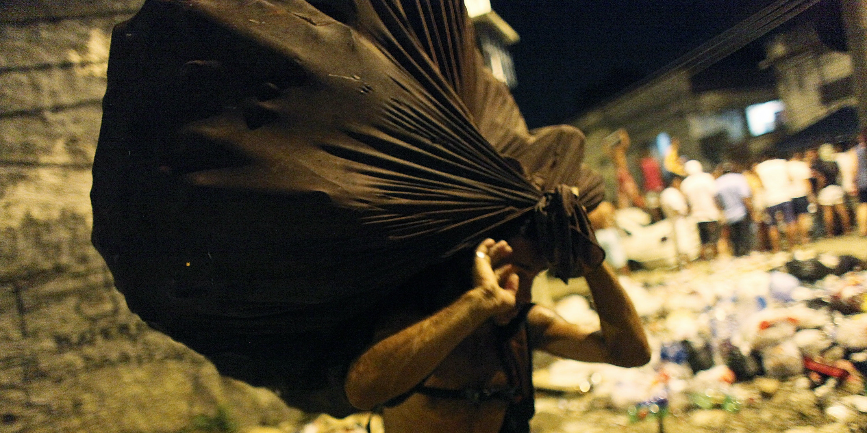 A waste picker carries a bag of collected recyclables past a street party thrown one block away from Rio's main red light district, Vila Mimosa.