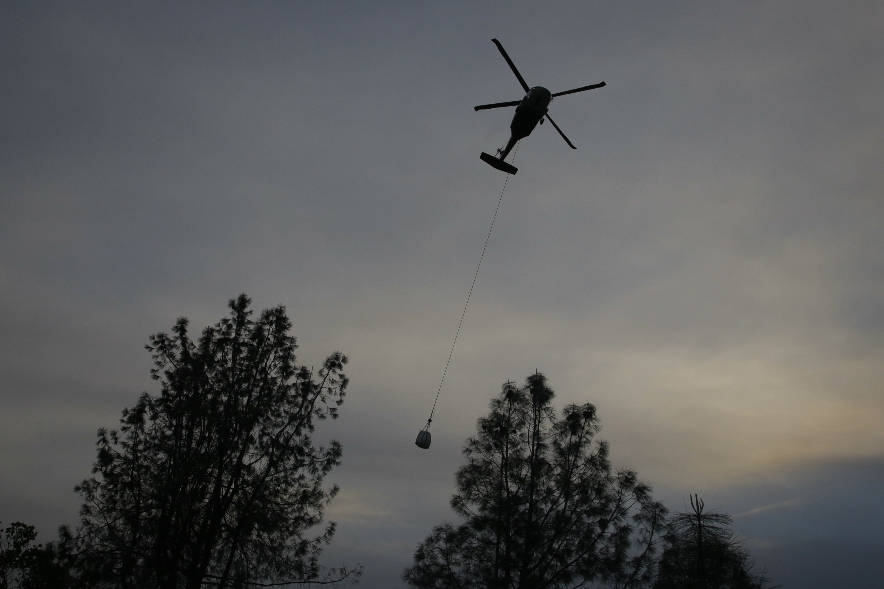 Helicopter carries large rocks to dump on main spillway of Oroville Dam.