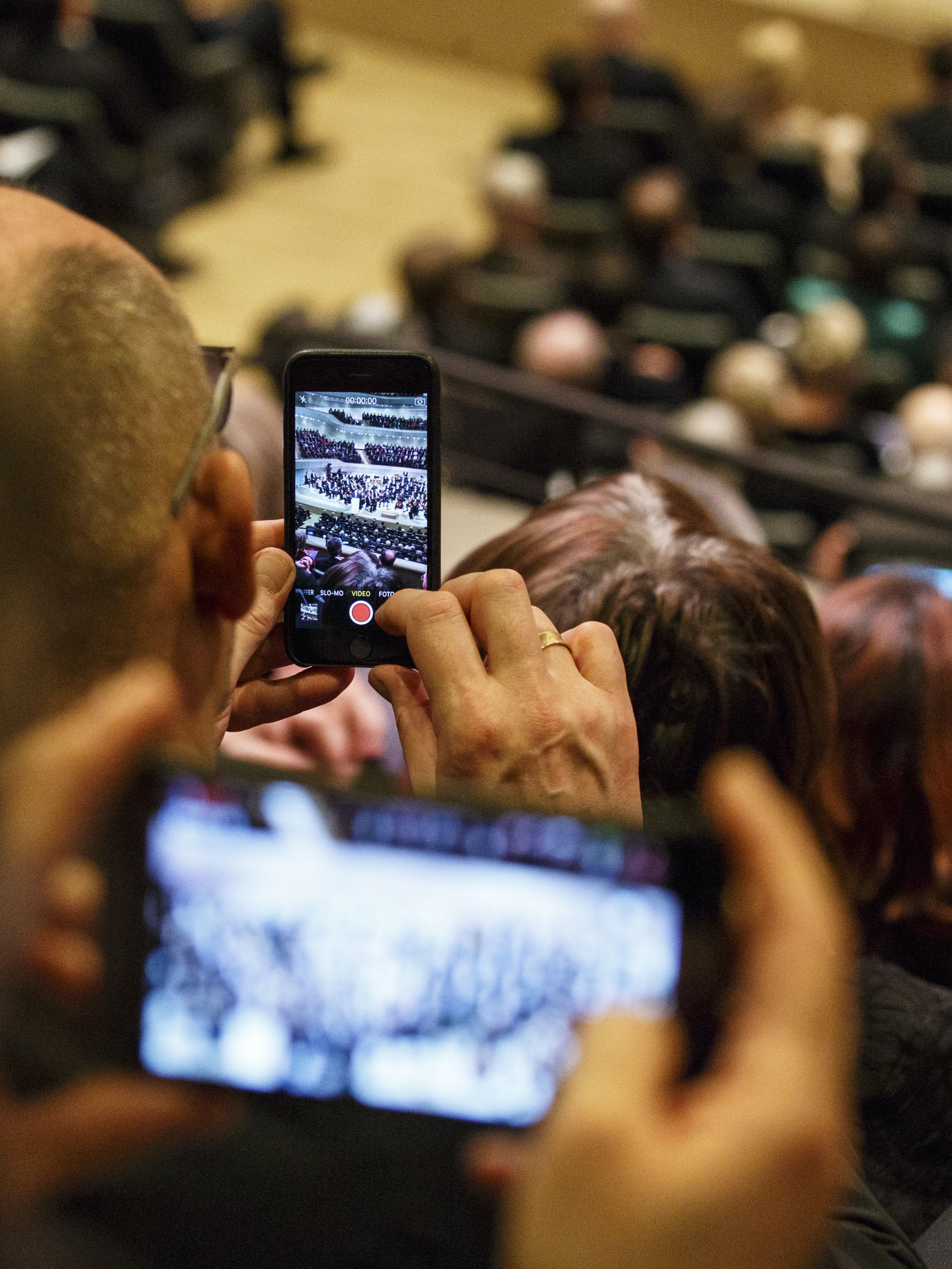 HAMBURG, GERMANY - JANUARY 11: Guest use thier smartphones as they attend the opening concert of the Elbphilharmonie concert hall on January 11, 2017 in Hamburg, Germany. Tonights opening gala comes around nine and a half years after the laying of the foundation stone, the new concert house sits ontop of an old warehouse building and is nicknamed 'Elphi' (Photo by Morris MacMatzen - Pool/Getty Images)