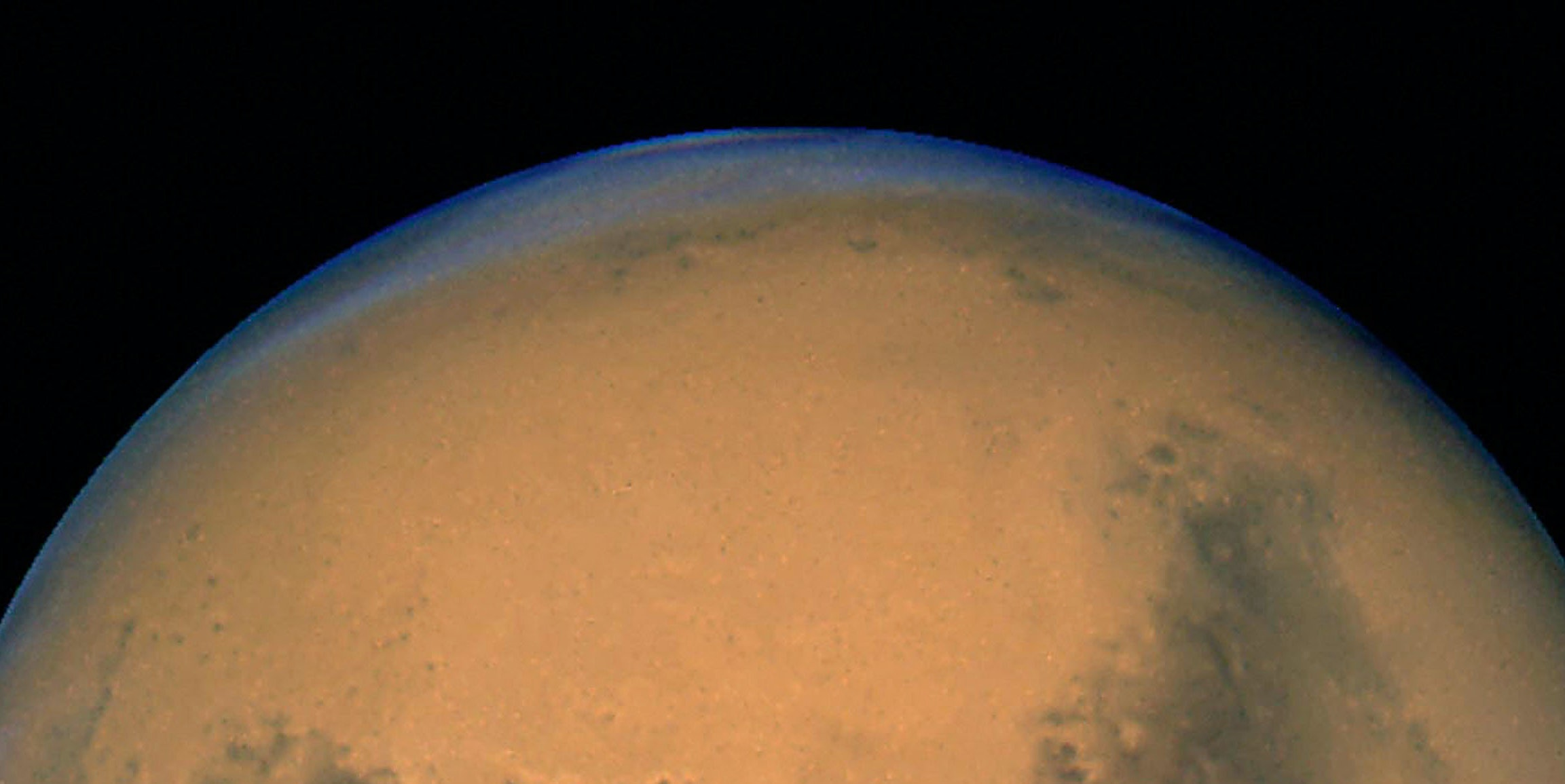 IN SPACE - AUGUST 26:  This image released August 27, 2003 captured by NASA's Hubble Space Telescope shows a close-up of the red planet Mars when it was just 34,648,840 miles (55,760,220 km) away. This color image was assembled from a series of exposures taken between 6:20 p.m. and 7:12 p.m. EDT  August  26, 2003 with Hubble's Wide Field and Planetary Camera 2. The picture was taken just 11 hours before the planet made its closest approach to Earth in 60,000 years. Many small, dark, circular impact craters can be seen, attesting to the Hubble telescope's ability to reveal fine detail on the planet's surface. (Photo by NASA/Getty Images)