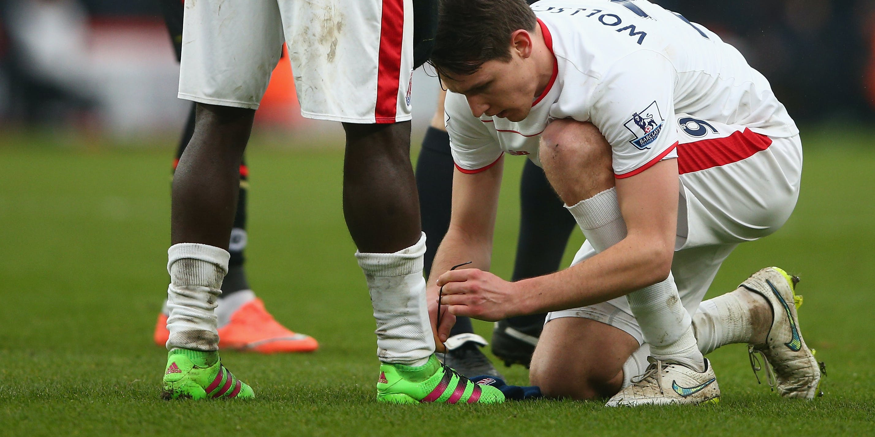 BOURNEMOUTH, ENGLAND - FEBRUARY 13: Philipp Wollscheid of Stoke City does up the shoelaces for Mame Biram Diouf during the Barclays Premier League match between A.F.C. Bournemouth and Stoke City at Vitality Stadium on February 13, 2016 in Bournemouth, England.  (Photo by Paul Gilham/Getty Images)