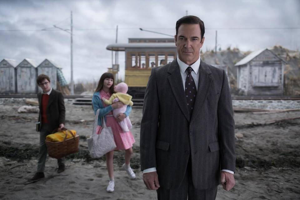 LEFT/BACK: Louis Hynes as Klaus Baudelaire, Melina Weissman as Violet Baudelaire, Presley Smith as Sunny Baudelaire. RIGHT/CENTER: Patrick Warburton as Lemony Snicket