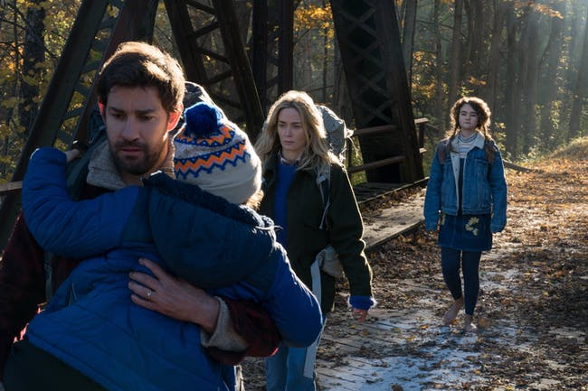 Lee Abbott (John Krasinski) carries his son Marcus (Noah Jupe) with his wife Evelyn (Emily Blunt) and daughter Regan Abbott (Millicent Simmonds) in the background.