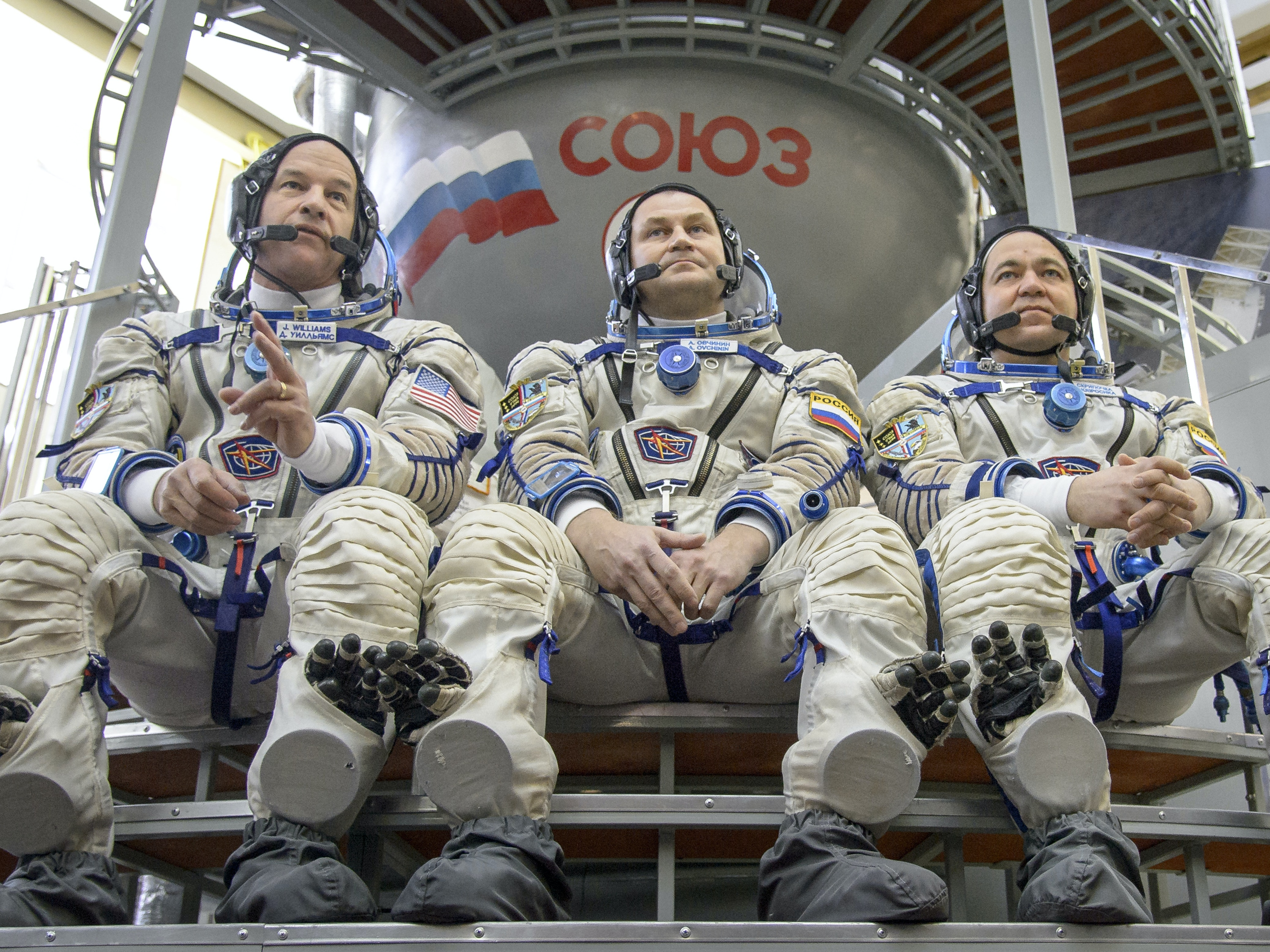 In this handout provided by NASA, Expedition 47 crew members: NASA astronaut Jeff Williams, left, Russian cosmonauts Oleg Skripochka, and Alexei Ovchinin of Roscosmos answer questions from the press outside the Soyuz simulator ahead of their final Soyuz qualification exams.