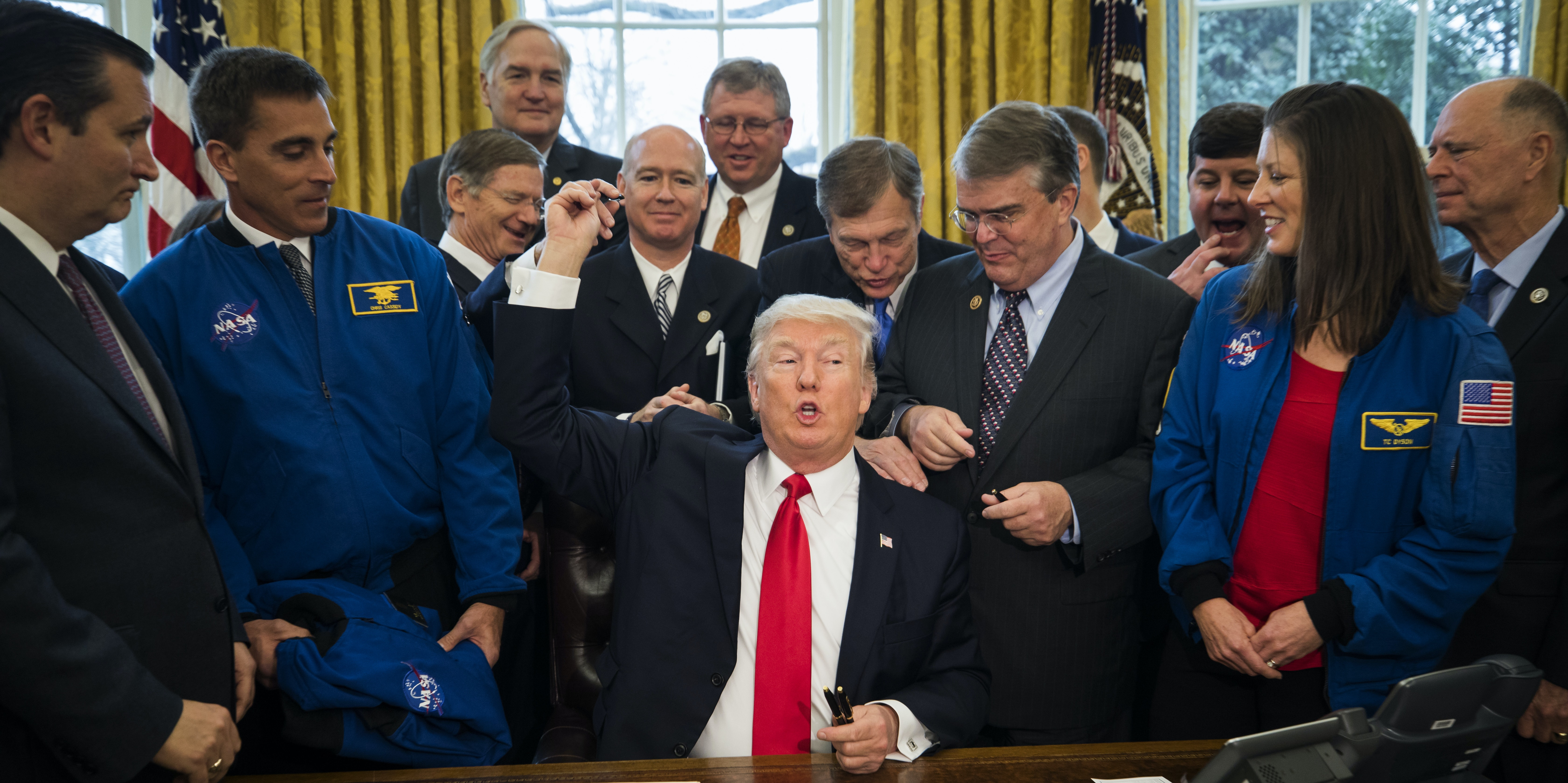 WASHINGTON, DC - MARCH 21:  U.S. President Donald Trump hands out pens after signing the NASA transition authorization act in the Oval Office of the White House March 21, 2017 in Washington, DC. The bill boosts NASA's overall budget $19.5 billion, while refocusing efforts on deep space exploration and a manned mission to Mars.  (Photo by Jim Lo Scalzo-Pool/Getty Images)
