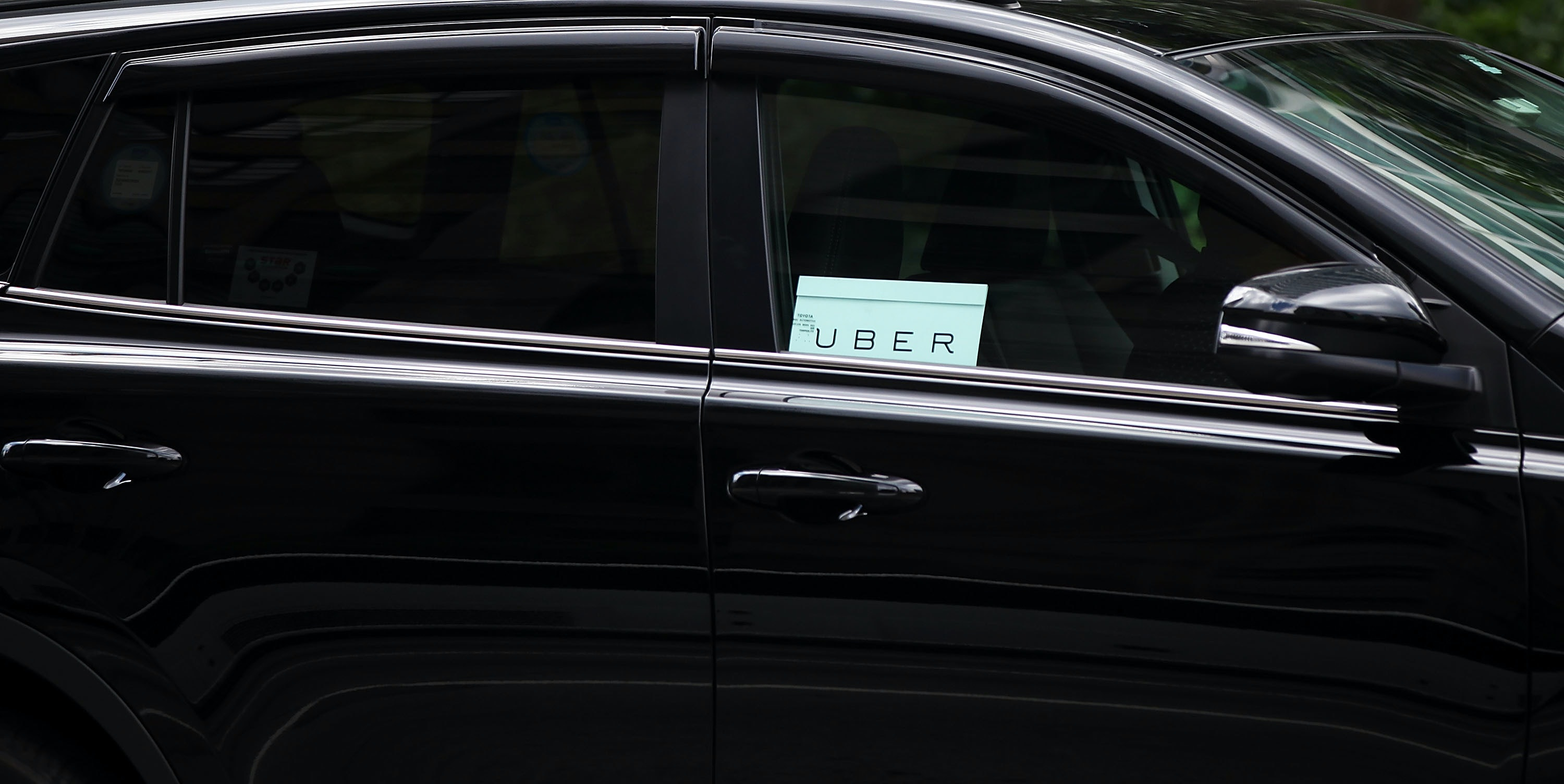 NEW YORK, NY - JULY 20:  An Uber vehicle is viewed in Manhattan on July 20, 2015 in New York City. New York's City Council has proposed two bills last month to limit the number of new for-hire vehicles, as well as to study the rapidly rising industry's impact on traffic. Uber has responded in an open letter arguing that its 6,000 Uber cars out during an average hour are a small part of the city's overall traffic. In cities across the globe Uber has upended the traditional taxi concept with many drivers and governments taking action against the California based company.  (Photo by Spencer Platt/Getty Images)