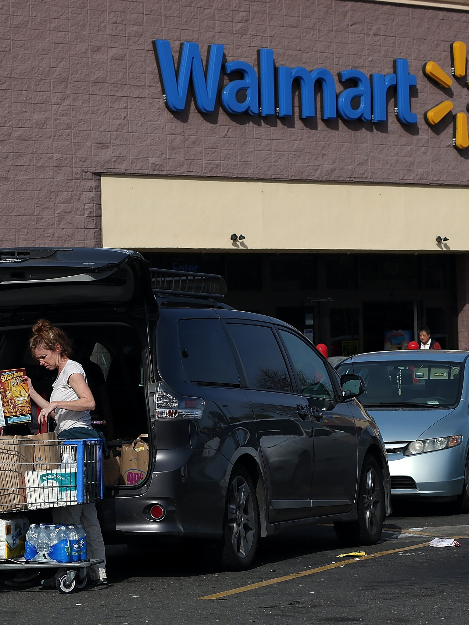 SAN LORENZO, CA - FEBRUARY 20:  A Wal-Mart customer loads groceries into her car outside of a Wal-Mart store on February 20, 2014 in San Lorenzo, California. Wal-Mart reporterd a 21 percent decline in fourth quarter earnings with profits of $4.4 billion or $1.36 a share compared to $5.6 billion, or $1.67 per share one year ago. (Photo by Justin Sullivan/Getty Images)