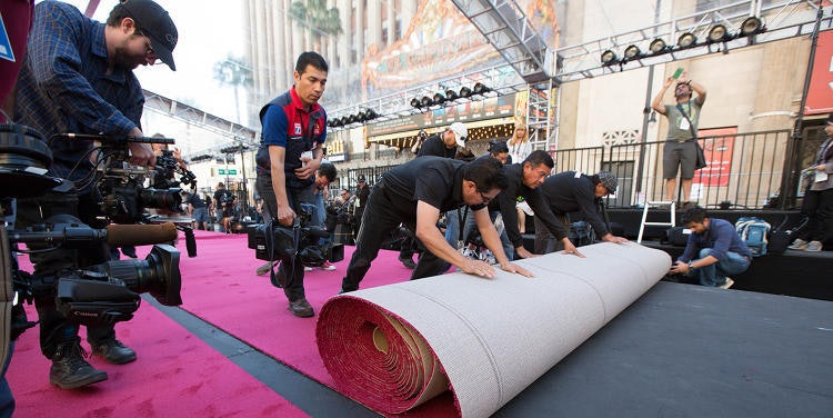 Professionals install sound-absorbent red carpeting for the Oscars pre-show earlier this weekend.