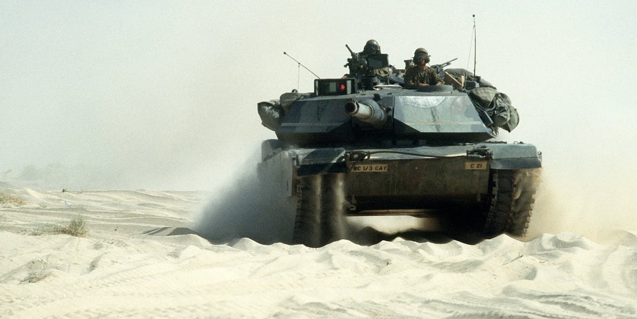 An M-1A1 Abrams main battle tank travels with a convoy on a desert road during Operation Desert Shield.