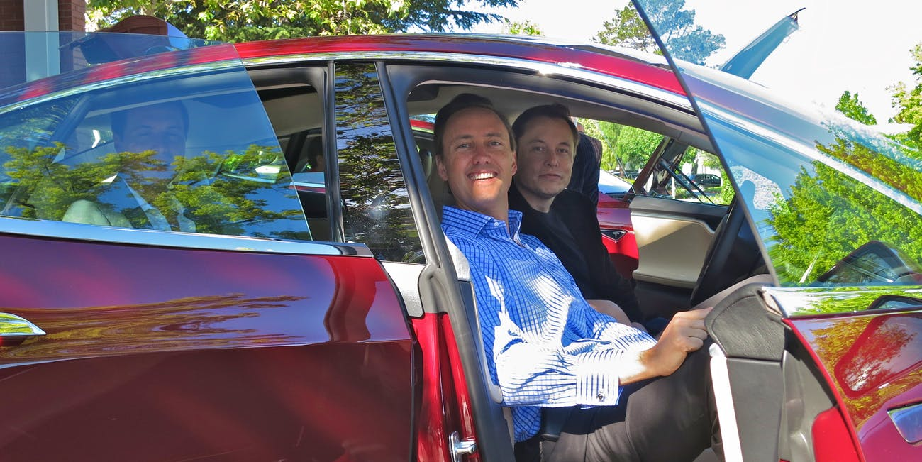 Kimbal and Elon Musk in a Tesla.