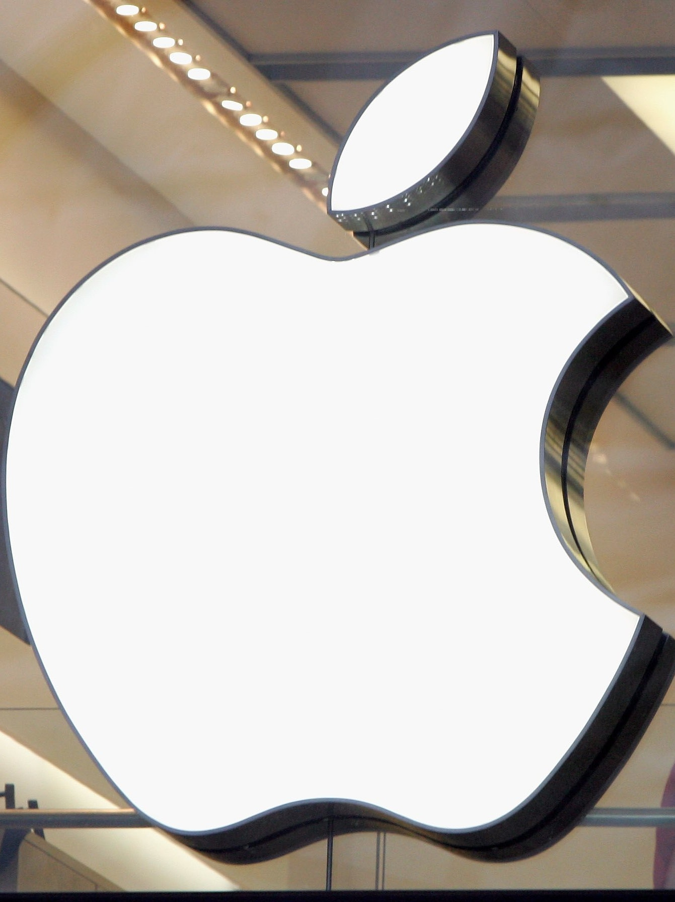 People are seen behind the Apple logo in Apple's flagship London retail store on Regent Street on December 27, 2006 in London, England.