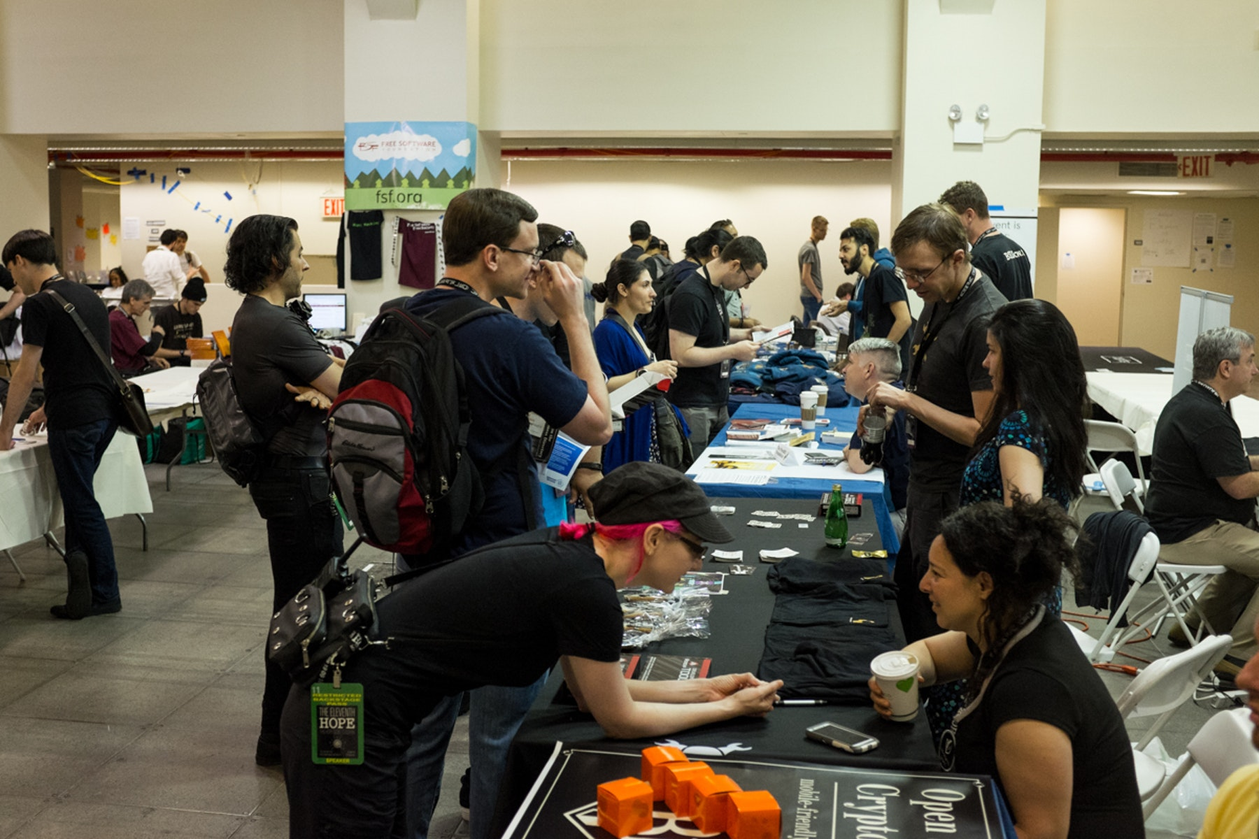 Attendees chat over various booths in HOPE's main concourse. Black is a popular color.