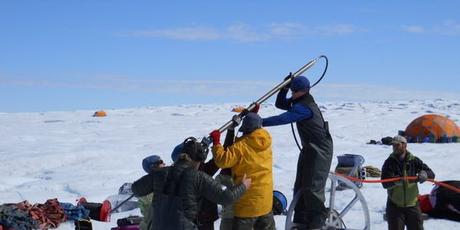 The crew of scientists prepare to put the drill stem into the Greenland ice sheet to probe water flows about a half of a mile below.