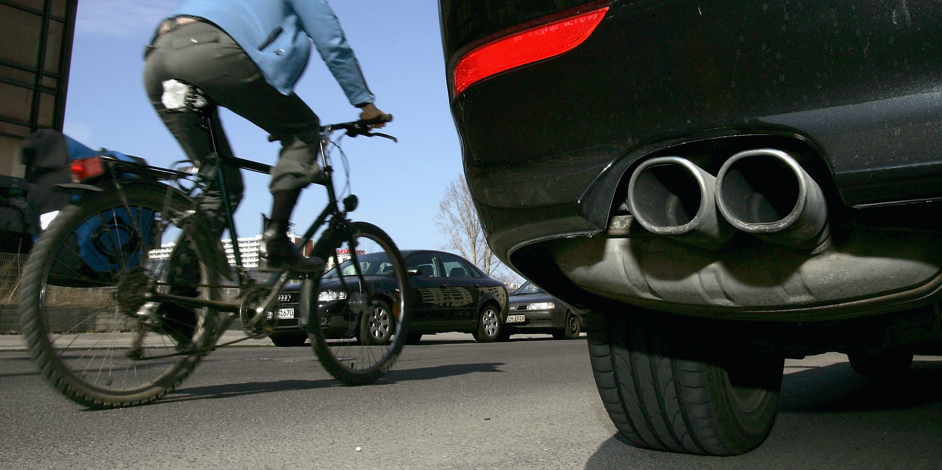 BERLIN, GERMANY - MARCH 29: A cyclist drives past a parked car and its exhaust pipe on March 29, 2005 in Berlin, Germany. Many German cities are close to violating EU-regulated emission limits of so-called fine particle dust, which mostly comes from diesel engines and worn tires. The German city of Munich recently exceeded its limit, and other cities, including Berlin and Frankfurt, are likely to do so soon. While other countries in Europe, such as Italy and France, have been dealing with the growing problem, Germany has lagged behind. An estimated tens of thousand of Germans die every year because of the medical consequences of breathing in fine particle dust. Several German automakers recently announced they will introduce particle filters for their diesel cars sooner than originally planned.    (Photo by Sean Gallup/Getty Images)