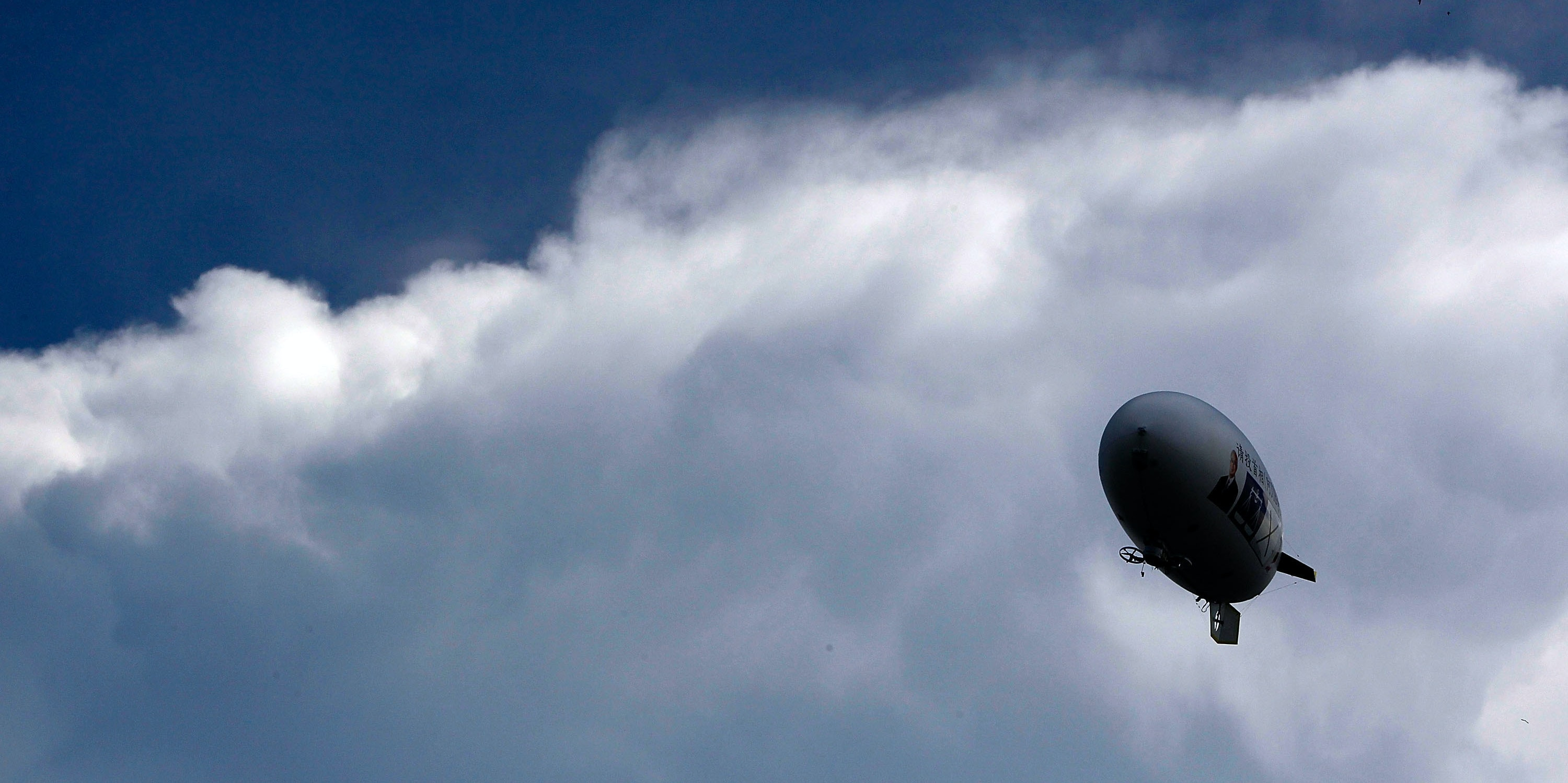 Officials release a blimp with a picture of Malaysia's Prime Minister .