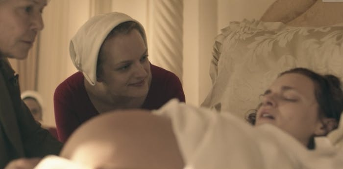 While the Wife goes through a simulated delivery, her Handmaid goes through an actual one.