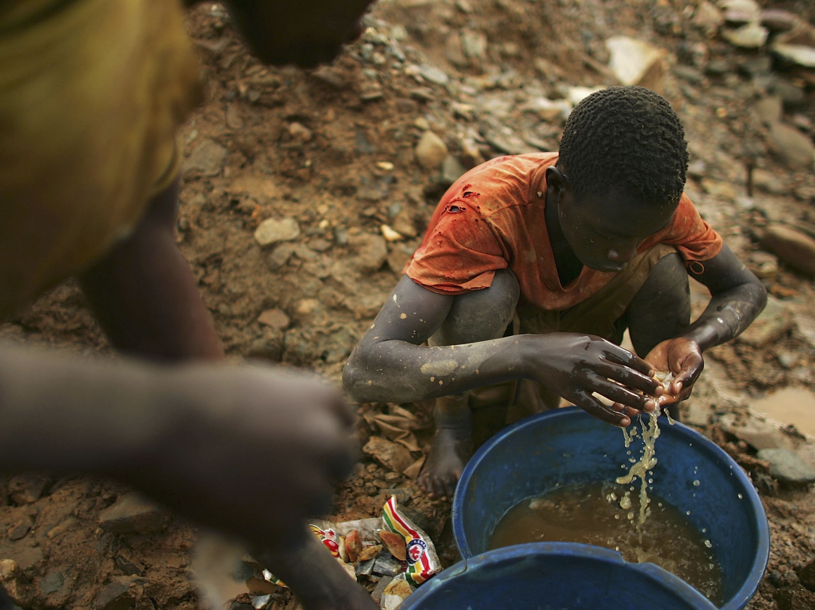 A child looks for gold in a mine in Congo. A similar process is used to find stray cobalt that falls off during the cleaning process.