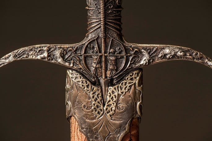 The crossguard of Heartsbane depicts the Tarly house sigil: the striding huntsman, aiming arrows towards the sigils of other Westerosi houses.