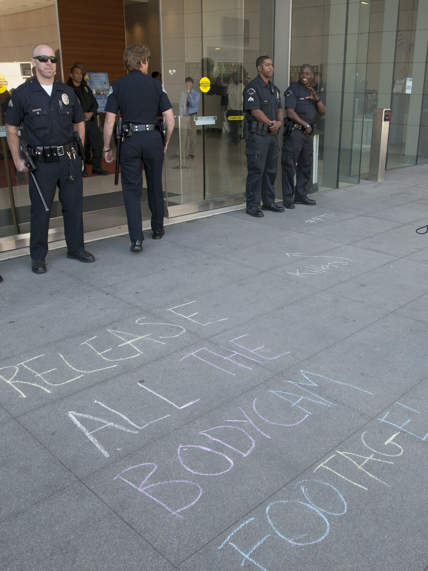 LOS ANGELES, CA - MARCH 3:  A man talks at officers at Los Angeles Police Department Headquarters near a chalk message calling for the release of the video from the body cameras worn by police officers involved in the fatal police shooting of an unarmed homeless man on March 3, 2015 in Los Angeles, California. Police say the homeless man, known by acquaintances as Africa, was shot dead by officers when he allegedly reached for the gun of one of several officers wrestling to the ground by his sidewalk tent. Amateur video of the controversial incident has been widely viewed over the internet    (Photo by David McNew/Getty Images)