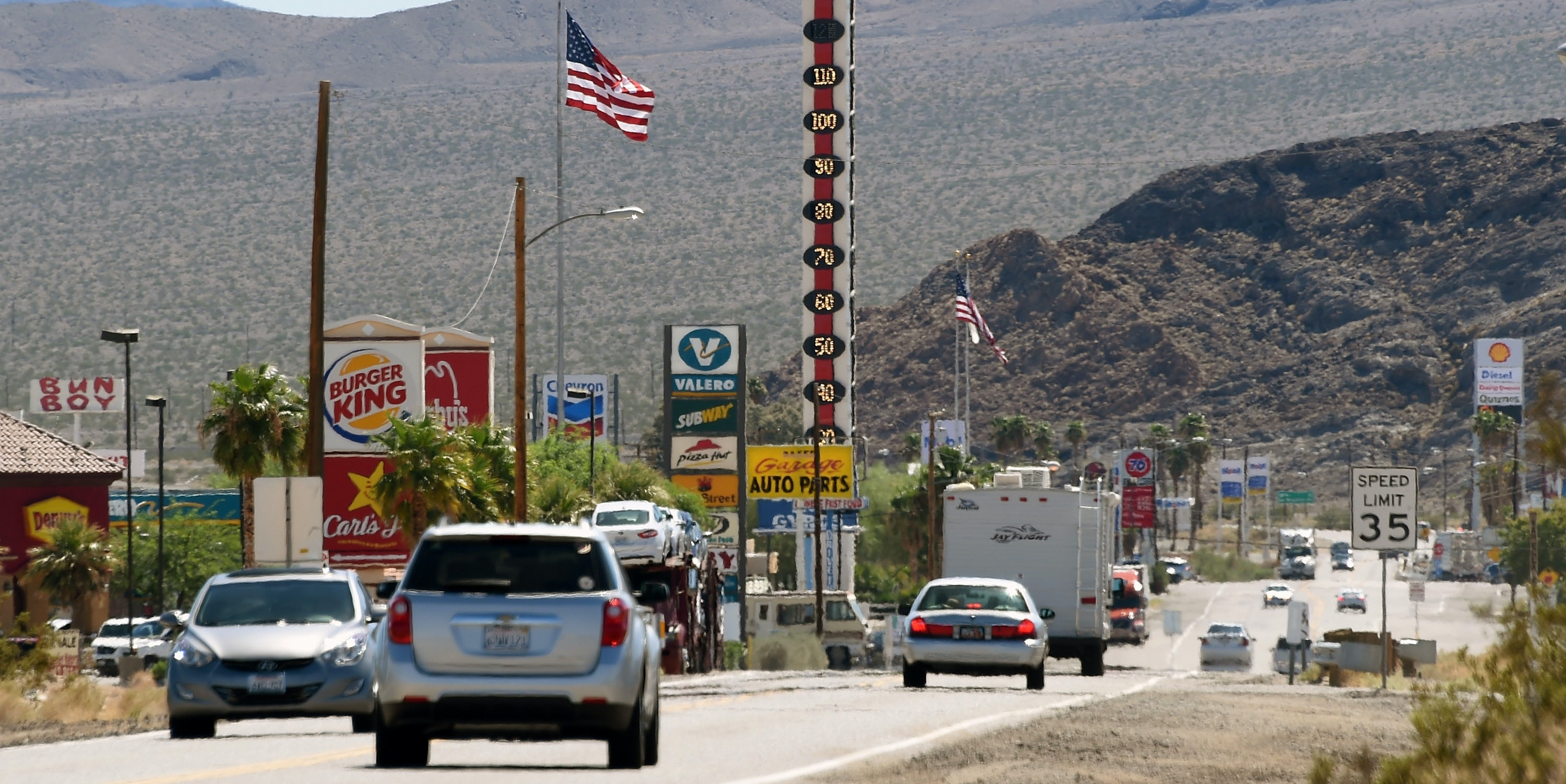 Vehicles drive by a 134-foot-high electronic sign displaying a temperature of 110 degrees Fahrenheit on July 23, 2014 in Baker, California.