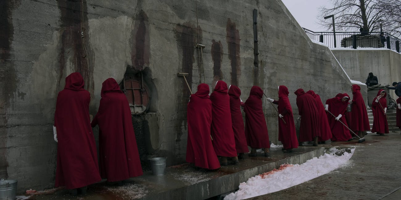 Handmaids clean the walls by the river in preparation for the arrival of a Mexican Trade Delegation.
