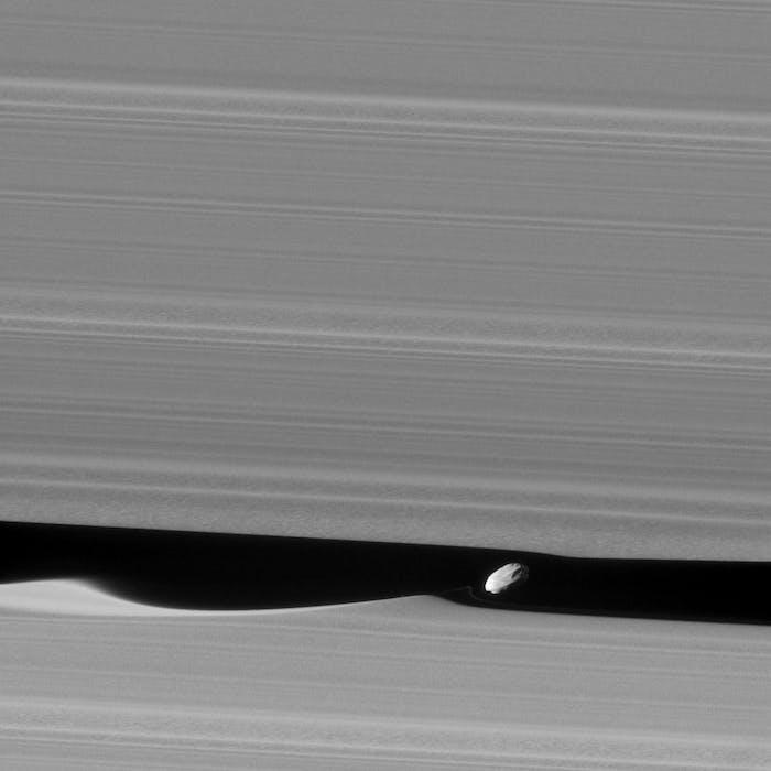 Daphnis orbits within Saturn's Keeler Gap, where it raises waves in Saturn's rings.
