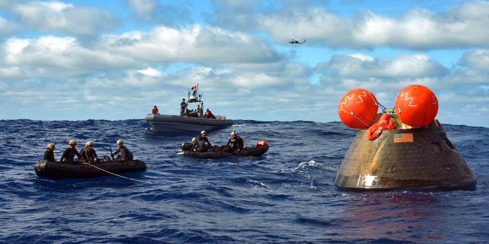 PACIFIC OCEAN - DECEMBER 05:  In this handout provided by U.S. Navy, Navy divers, assigned to Explosive Ordnance Disposal Mobile Unit 11 (EODMU11), Mobile Dive and Salvage Company 11-7, attach a towing bridal to the Orion Crew Module during the first Exploration Flight Test (EFT-1) NASA Orion Program following its launch from Cape Canaveral Air Force Station's Space Launch Complex 37 December 5, 2014 in the Pacific Ocean, 600 miles southwest of San Diego. The Orion spacecraft orbited Earth twice, reaching an altitude of approximately 3,600 miles above Earth before landing. The amphibious transport dock USS Anchorage (LPD 23) is currently conducting the first exploration flight test (EFT) for the NASA Orion Program.  (Photo by U.S. Navy via Getty Images)
