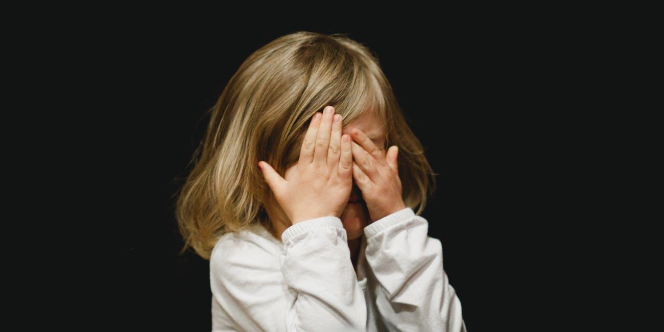little girl covering her eyes