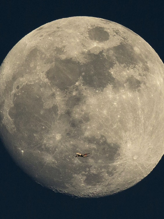 A plane flies past the moon at sunset on March 3, 2015 in London, England.