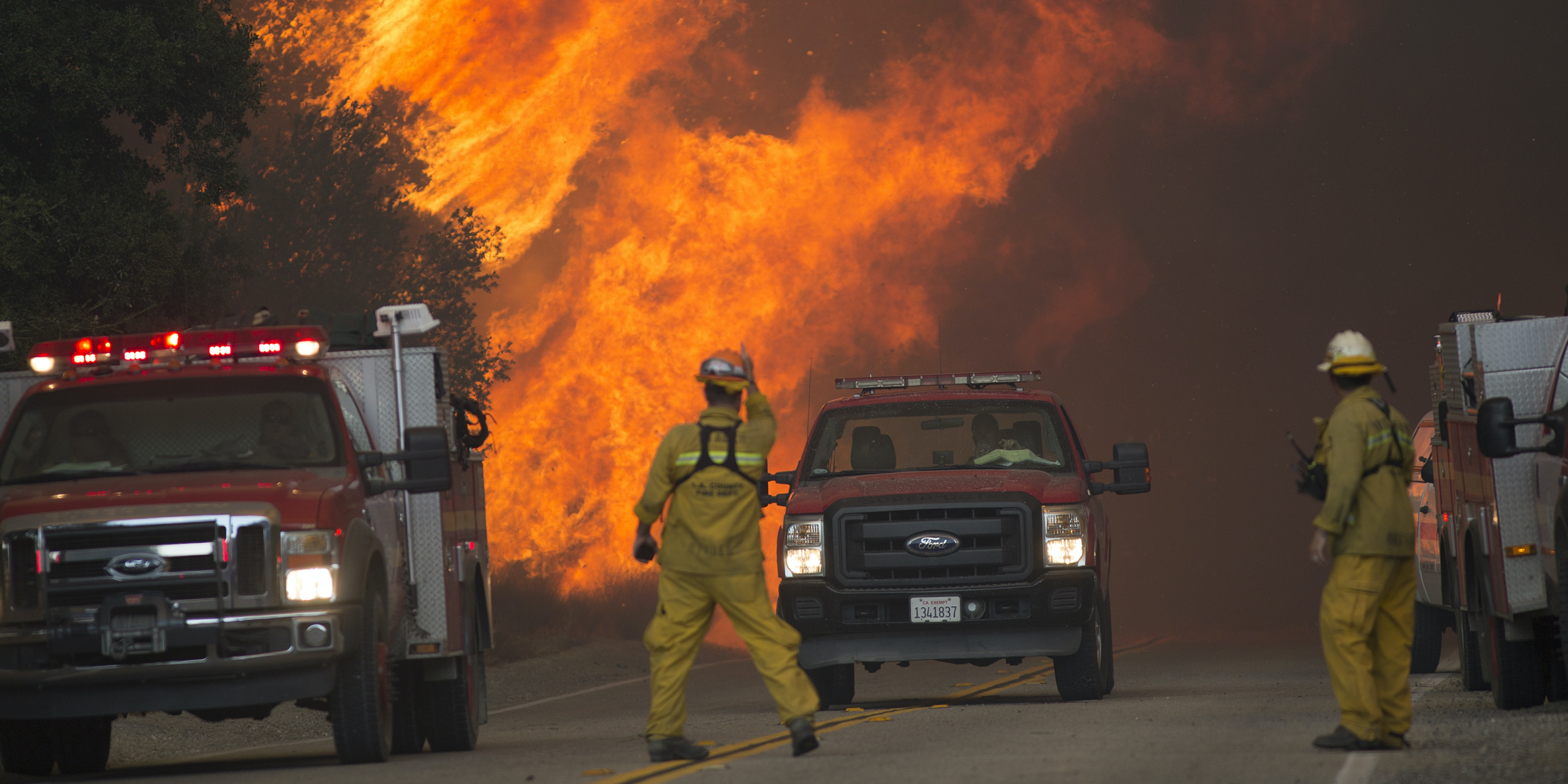 Firefighters are forced to retreat as flame close in on them in Placerita Canyon at the Sand Fire on July 24, 2016 in Santa Clarita, California. Triple-digit temperatures and dry conditions are fueling the wildfire, which has burned across at least 22,000 acres so far and is only 10% contained.