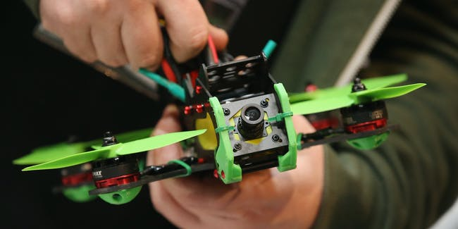 A drone racing enthusiast prepares a small multirotor racing drone in the Dronemasters hall at the 2016 CeBIT digital technology trade fair on the fair's opening day on March 14, 2016 in Hanover, Germany.