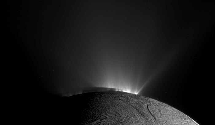 The geyser basin at the south pole of Enceladus, with its water plumes illuminated by scattered sunlight.