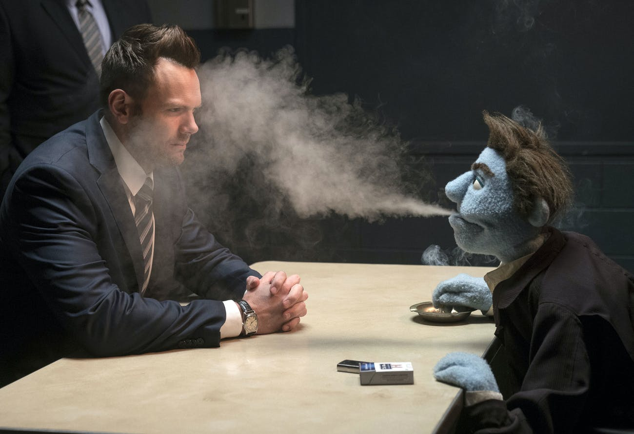Phil Philips blasts an impossible amount of cigarette smoke into the face of Joel McHale's FBI agent.