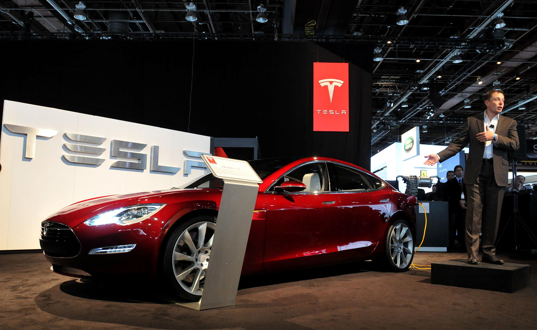 Elon Musk showing off a Tesla.