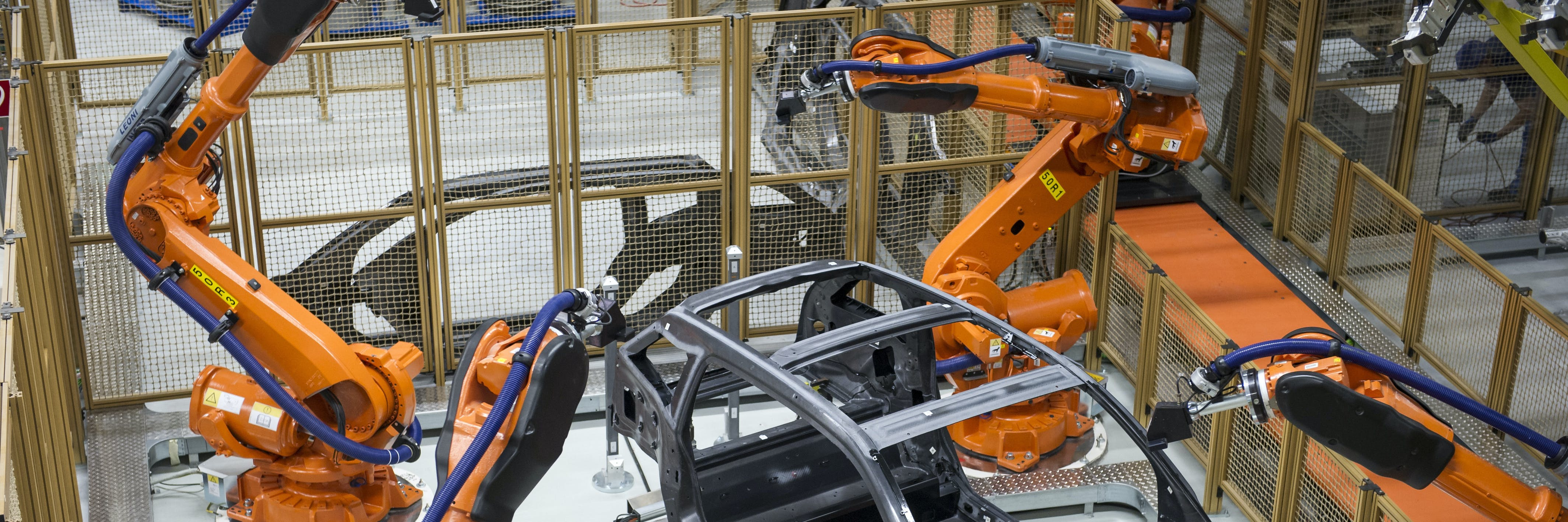 LEIPZIG, GERMANY - SEPTEMBER 18:  Robots manufacture a carbon chassis of a new BMW i3 electric car on the assembly line at the BMW factory on September 18, 2013 in Leipzig, Germany. The i3 is BMW's first mass market electric car and the company has invested EUR 400 million into its production at the Leipzig factory. (Photo by Jens Schlueter/Getty Images)