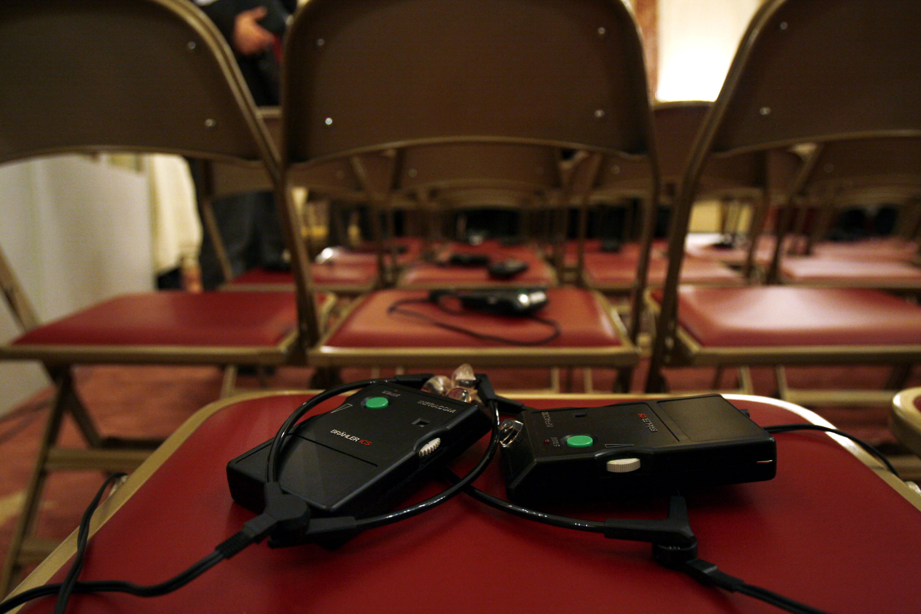 Headphones for translation purposes left by audience members sit on chairs after the conclusion of a press conference.