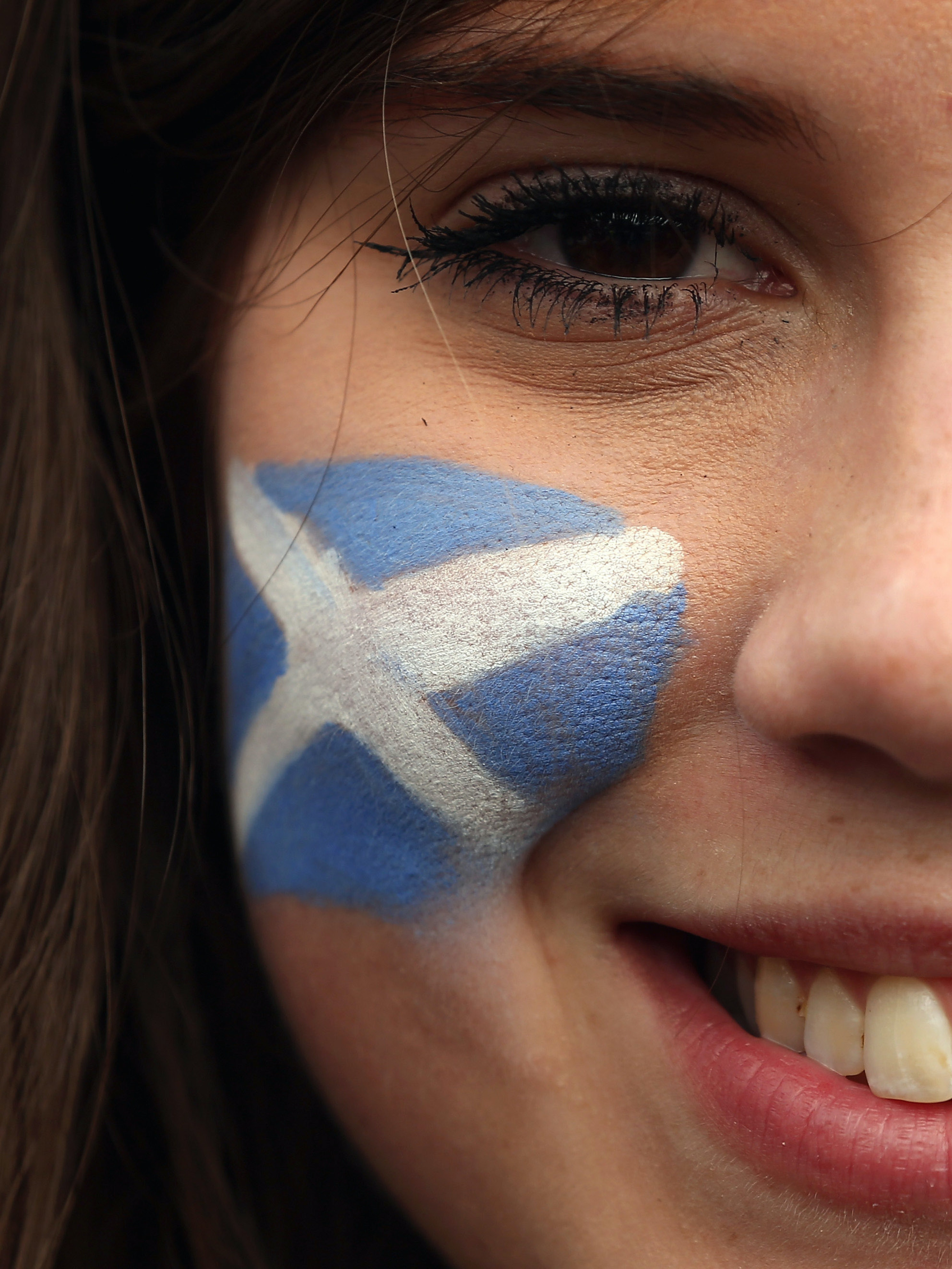 LONDON, ENGLAND - AUGUST 14:  A fan with the Scotland flag face-painted on her cheeks smiles as she arrives at Wembley Stadium ahead of a friendly match between England and Scotland on August 14, 2013 in London, England. Scotland and England will meet at Wembley stadium tonight for their first international in 14 years.  (Photo by Dan Kitwood/Getty Images)