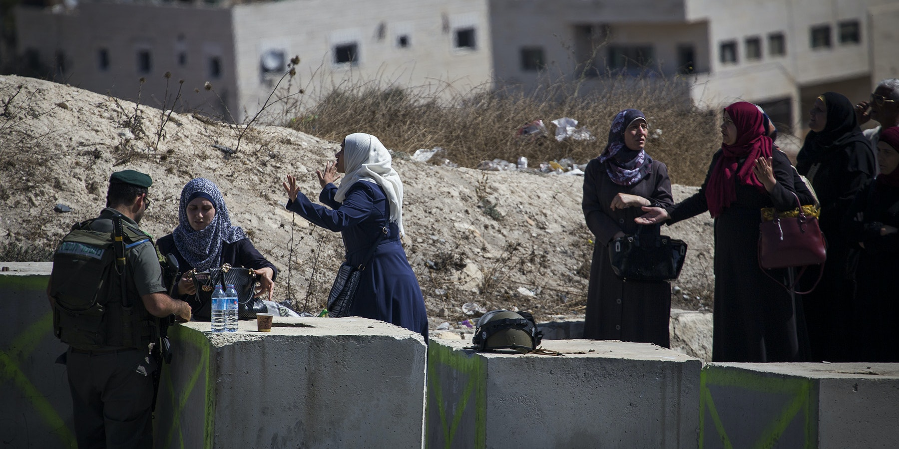 Israeli soldiers search Palestinians at a border checkpoint.