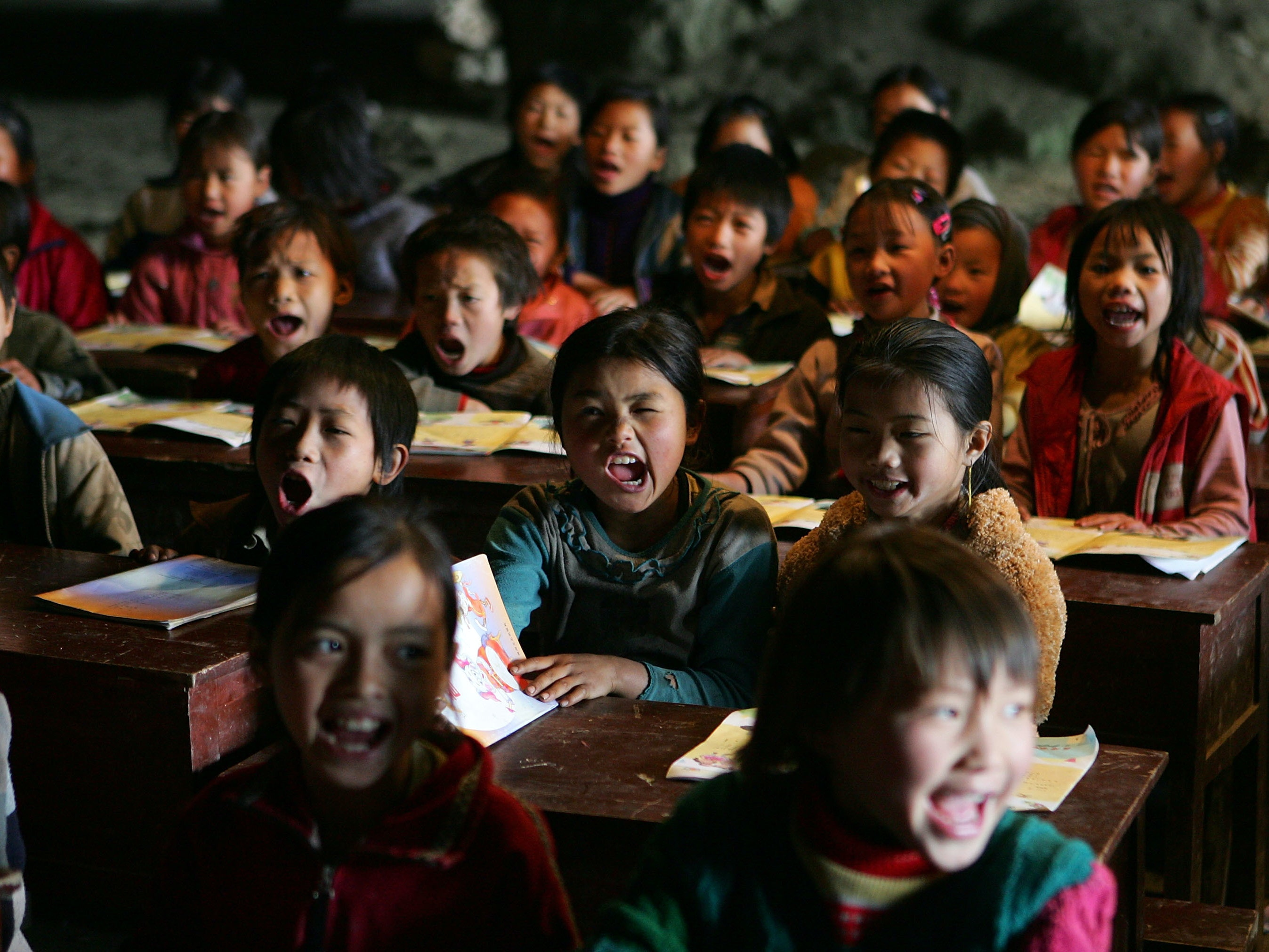 ZIYANG COUNTY, CHINA - MARCH 16:  Children learn a song in music class at their school in a huge cave at a remote Miao village March 16, 2007 in Ziyun county, Guizhou province of southwest China. The Middle Cave elementary school, which has 194 students in five classes, was built inside the natural cave 20 years ago by 16 Miao families who have lived there for more than half a century. Most of the students must walk for one to three hours on a stone path to get the school every morning.  (Photo by Cancan Chu/Getty Images)
